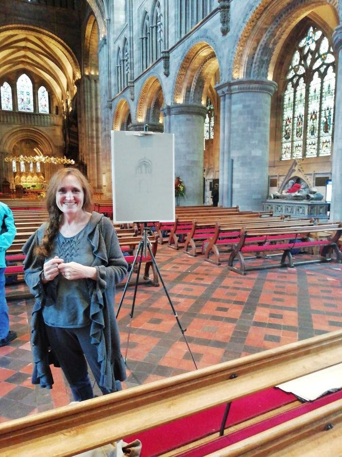 Linda stands smiling in the Nave of the cathedral in front of an easel