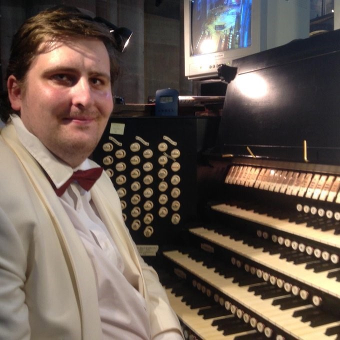 Stephen sits at the organ and smiles for the camera. He is wearing a suit and bow tie.