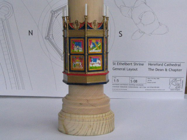 A small scale model of the shrine. It is set around a pillar and features brightly coloured panels with candles at the top of each panel