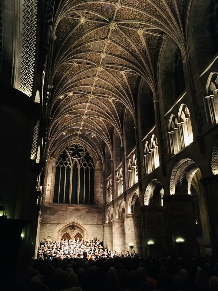 A photograph of the cathedral facing towards the West End where the Choral Society are stood. The building is full and in darkness with the lights highlighting the architecture