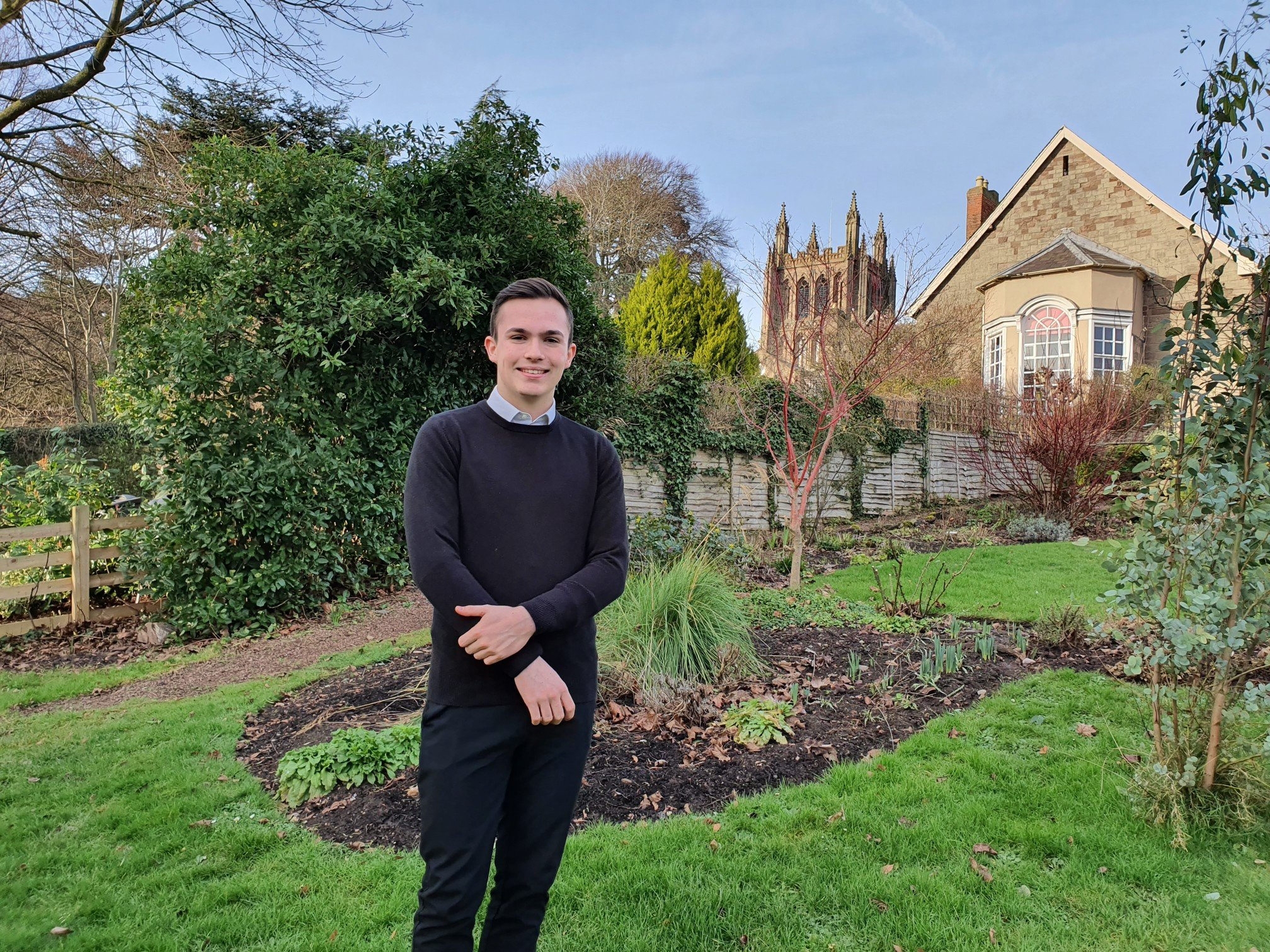 Ollie Fulwell standing in the Canons Garden with the cathedral tower in the background. It is sunny and he is smiling for the camera